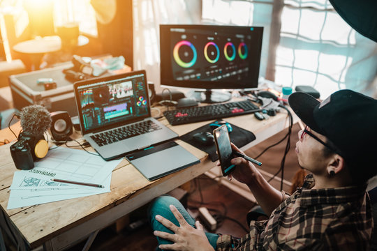 The content creator using mobile working  with the laptop editing video footage in the house studio of freelancer man