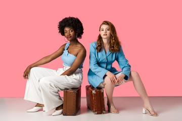 attractive multicultural women sitting on suitcases on pink Wall mural