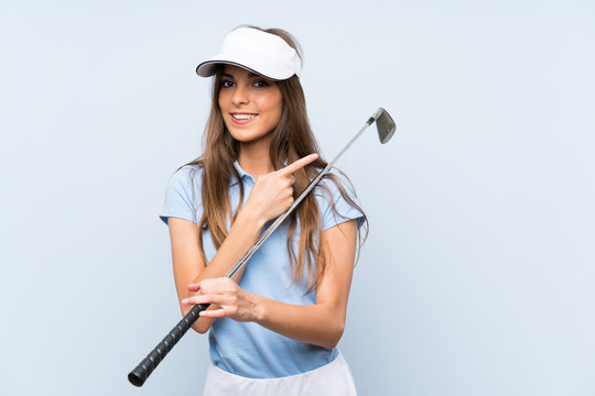 Young golfer woman over isolated blue wall pointing to the side to present a product