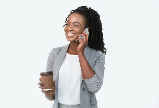Smiling Afro Businesswoman Talking On Cellphone Holding Coffee Cup, White Background