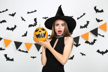 Beautiful woman in black costume holding halloween pumpkin with paper bats and flags on white background Wall mural