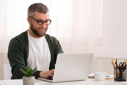 Middle aged man enjoying his job, working from home