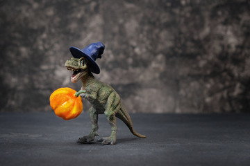 Dinosaur and halloween pumpkin on black background. fall season. Tyrannosaurus Rex in wizard's hat holding a pumpkin. Creative design autumn time idea, halloween holiday minimalism concept. copy space