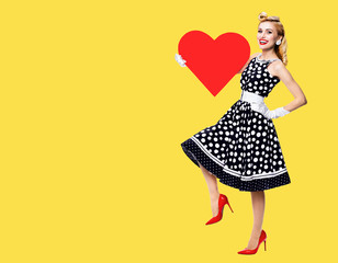 Full body of happy woman holding red heart symbol, dressed in pin up style black dress with white polka dot, isolated over yellow color background