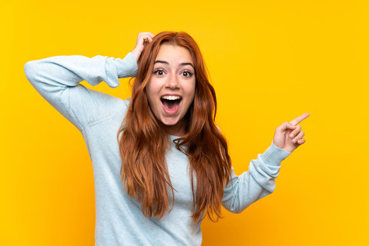 Teenager redhead girl over isolated yellow background surprised and pointing finger to the side