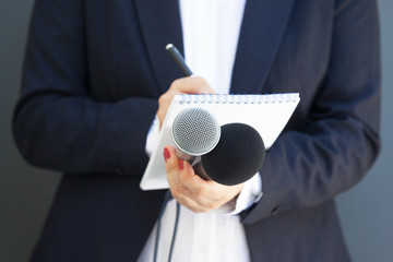 Female journalist at news conference or media event, writing notes, holding microphone