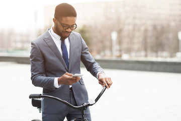 Modern businessman going to office by bike, using phone
