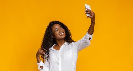 Flirting african girl making selfie on her smartphone