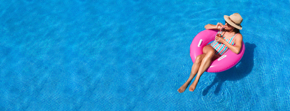 Young woman with sunglasses, hat and swimsuit in a blue pool. Pretty girl on a pink float enjoying the summer while having a cocktail.