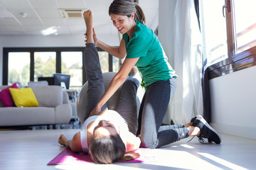 Physiotherapist helping to beautiful pregnant woman for doing pilates exercises with ball preparing for childbirth.