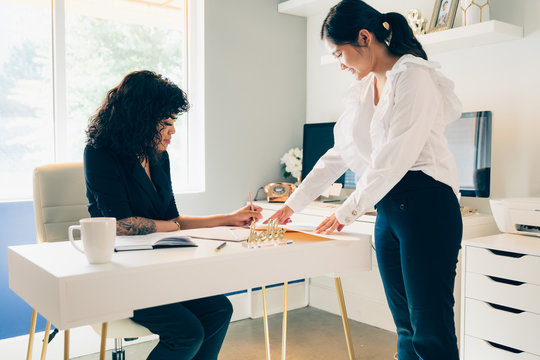 Direct view of two young businesswomen in modern office space