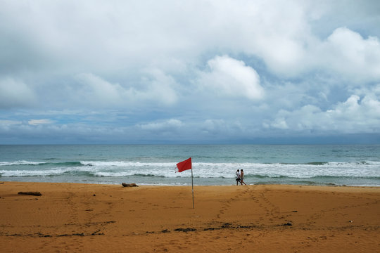 A couple walks on the beach as a red flag announcing rip currents waves as Tropical Storm Karen approaches in Luquillo