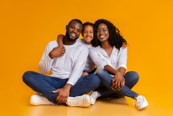Happy African American Family of Three Over Yellow Background