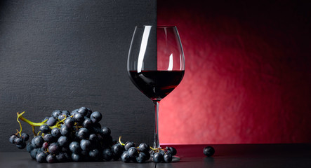 Red wine grapes on a black table and glass of red wine. Fototapete