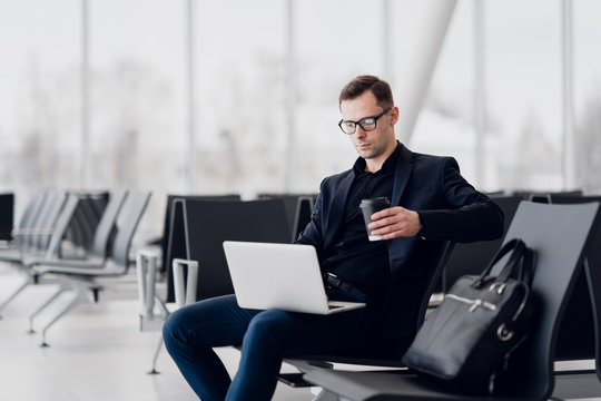 Handsome young businessman working on a laptop and drinking a coffee during an expectation of a flight