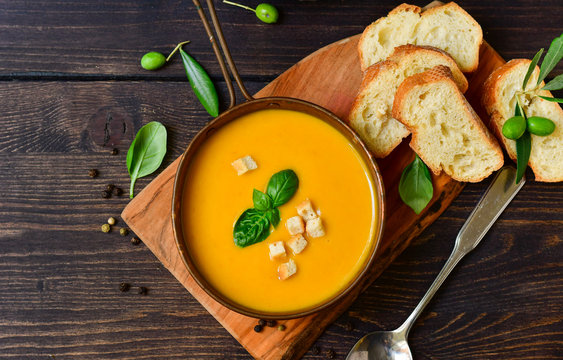 pumpkin soup and bread with basil and crispy crackers, vegan recipe. Autumn cream soup of seasonal product