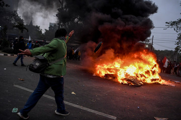 A protester throws a tire in a fire during university students' protest outside the Indonesian Parliament in Jakarta