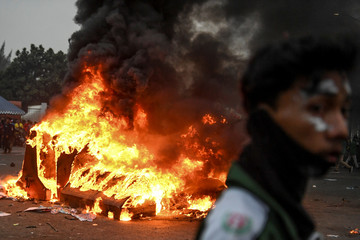 A protester is pictured next to a fire during university students' protest outside the Indonesian Parliament in Jakarta