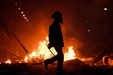 A protester walks near a fire during university students' protest outside the Indonesian Parliament in Jakarta