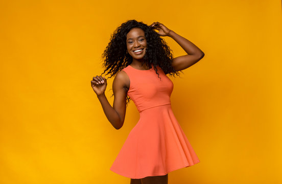 Joyful african girl in summer dress turning around