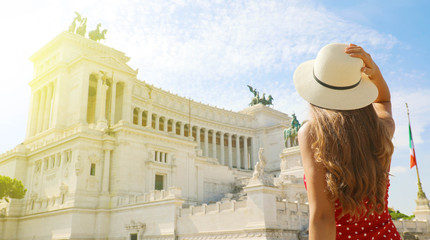 Travel in Rome. Back view of beautiful girl visiting Altar of the Fatherland famous landmark of Rome. Summer holidays in Italy.