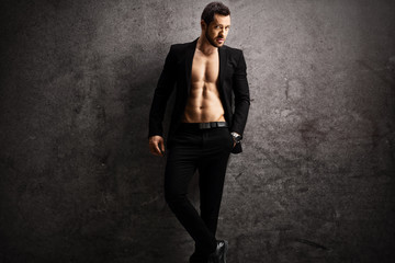 Handsome man in a black suit posing shirtless