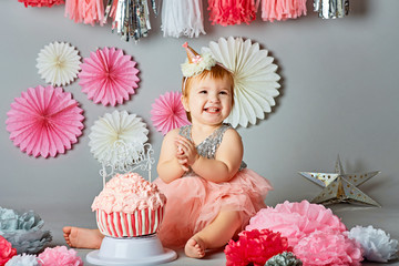 little girl smashes a cake on his first birthday. Smash cake, stylized photo session for a children's party