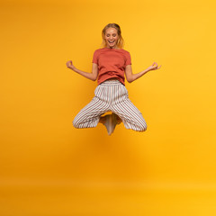Obraz Blonde girl jumps in yogas position. Relax concept. Yellow background - fototapety do salonu