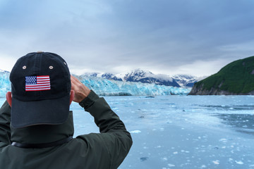 Man in hat with USA flag is taking a photo of a Hubbard Glacier. He is on a cruise in Alaska. Expedition to the glaciers
