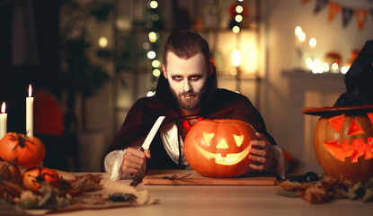 happy Halloween!  bearded man in a Dracula vampire costume with a pumpkin in dark home.