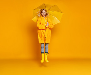 young happy emotional girl laughing  with umbrella   on colored yellow background.