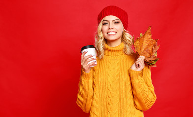 happy emotional cheerful girl laughing  with knitted autumn cap and Cup of coffee on colored red background. Wall mural