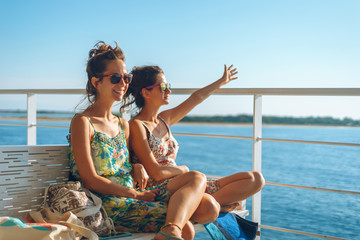 Two young women girl friends or sisters sitting on the bench on the deck of the ferry boat or ship sailing to the island tourist destination on summer vacation waving to the horizon in sunny day