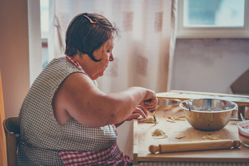 italian woman make homemade pasta ravioli on wood board