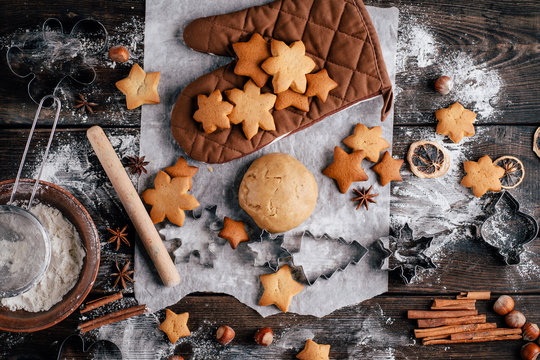 Freshly baked appetizing homemade gingerbread cookies, raw dough, baking utensils and food decorations. Christmas and New Year celebration traditions. Family home bakery, cooking festive sweets