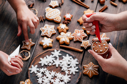 Christmas and New Year celebration traditions, festive sweets, family culinary. Traditional gingerbread. Friends decorating freshly baked cookies with icing and mastic