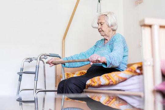 Elderly 96 years old woman exercising with a stick sitting on her bad. Geriatric health care home assisted support for older people concept. Care for the elderly.
