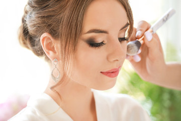 Professional makeup artist working with young bride at home, closeup