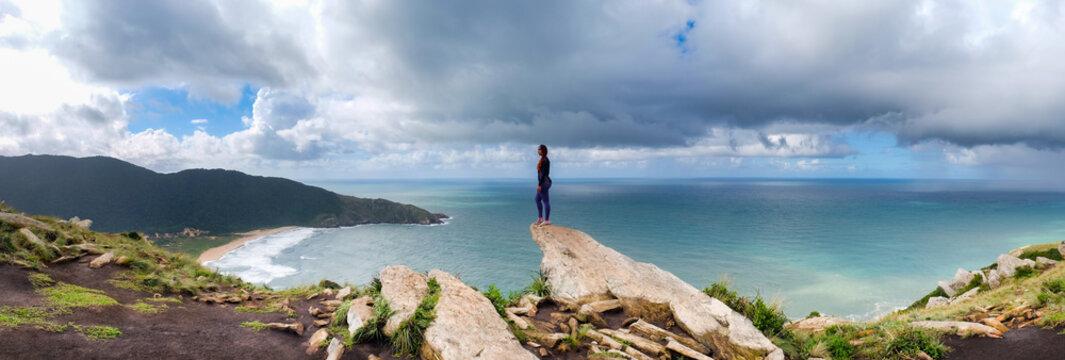 Panorámica de mujer en la cima de una montaña observando un mar y su playa con montañas verdes de fondo