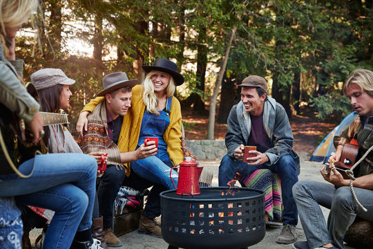 Group of friends camping around fire