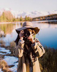 young cute girl in a hat holding a camera in her hands. she photographs the landscape