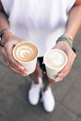 Summer street closeup of young beautiful hands holding two takeaway paper cups with cappuccino