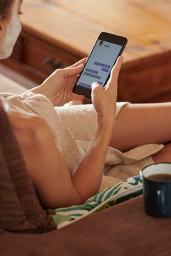 Woman relaxing at home and chatting via phone