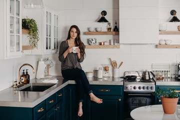 Woman Sitting on Kitchen Counter Drinking Coffee