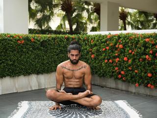 Shirtless tattooed man balancing in lotus