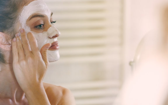 Young woman applying cleansing mask