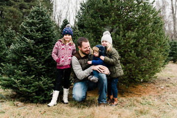 Father with his three kids in Christmas tree farm,