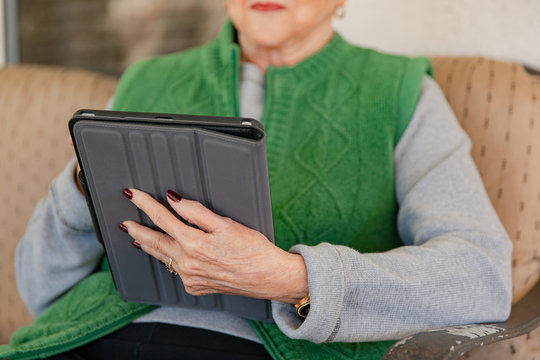 A mature woman sitting on her patio, using her tablet device.