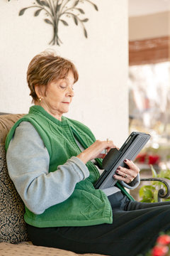 A senior woman sitting on her patio, using her tablet device.