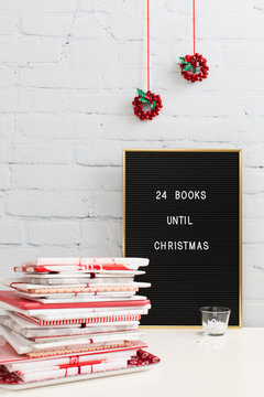 """Pile of books wrapped in paper close to board saying """"""""24 books to Christmas"""""""""""